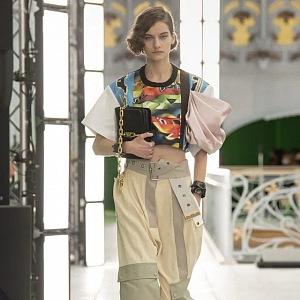 Žena v béžových kalhotách a barevném topu LV SS2021