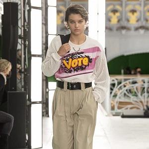 Žena v béžových kalhotách a bílém topu LV SS2021