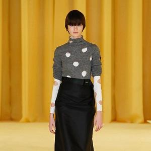 Žena v černé sukni a pleteném svetru Prada SS2021