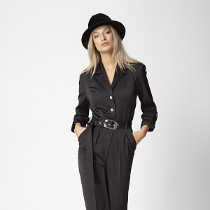 Žena v černém overalu a klobouku.