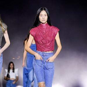 Žena v červeném topu a denimových šorktách Balmain SS2021