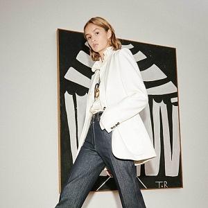 Žena v džínách a bílém saku Victoria Beckham