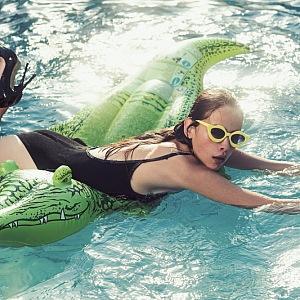 Žena v lodičkách z krokodýlí kůže leží na nafukovacím krokodýlovi