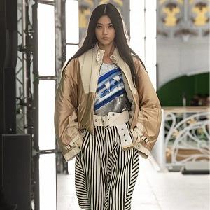 Žena v pruhovaných kalhotách a béžové bundě Louis Vuitton SS2021
