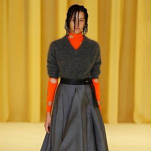 Žena v šedé sukni a topu Prada SS2021