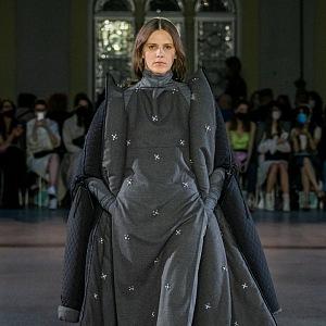 Žena v šedém outfitu s aplikací od Jakiba Polanky